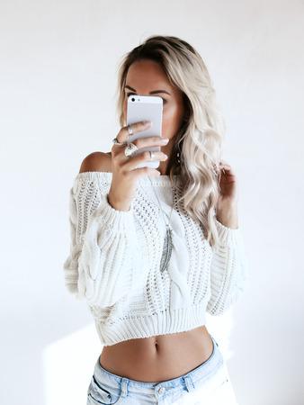 ブロンドの女の子が鏡の中の彼女のスマート フォンで selfie を作って白のセーターとジーンズのショート パンツを着用します。自己ファッションを