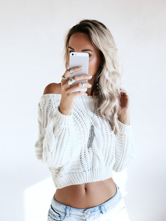 Blond girl wearing white sweater and jeans shorts making selfie by her smartphone in the mirror. Blogger taking photo of self fashion look. Stock Photo