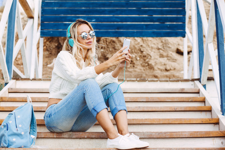 relaxing beach: Young woman with backpack wearing sweater and jeans relaxing and listening music at the beach, autumn weekend on the sea shore