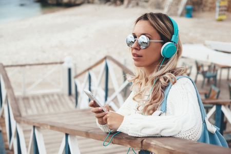 autumn young: Young woman with backpack wearing white sweater relaxing and listening music at the beach, autumn weekend on the sea shore Stock Photo