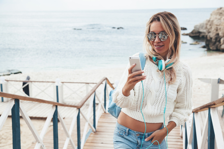 autumn young: Young woman with backpack wearing sweater and jeans relaxing and listening music at the beach, autumn weekend on the sea shore