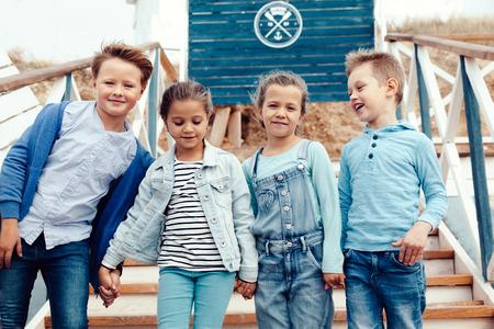 海の海岸で楽しんでデニム服を着てファッション子供のグループ。ブルーとネイビーの色の秋のカジュアルな服。7-8 歳のモデル。