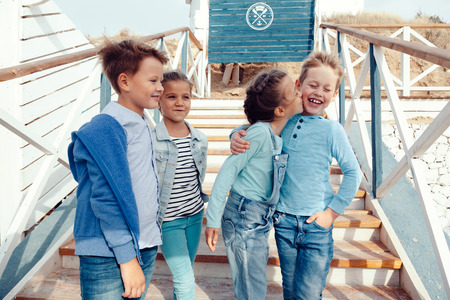 boy kid: Group of fashion children wearing denim clothing having fun on the sea shore. Autumn casual outfit in blue and navy color. 7-8 years old models.