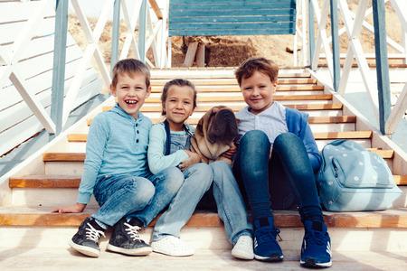 mezclilla: Grupo de niños de la manera que usan ropa vaquera con el perro que se divierte en la orilla del mar. traje casual otoño en color azul y azul marino. modelos de 7-8 años de edad.
