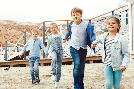 fashion boy: Group of fashion children wearing denim clothing running on the sea shore. Autumn casual outfit in blue and navy color. 7-8 years old models.