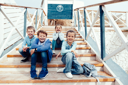 fashion boy: Group of fashion children wearing denim clothing having fun on the sea shore. Autumn casual outfit in blue and navy color. 7-8 years old models.