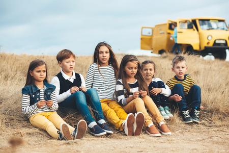 Grupo de niños de manera que desgasta misma ropa del estilo que se divierte en el campo de otoño. Caída traje casual en color azul marino y amarillo. modelos 7-8, 8-9, 9-10 años de edad. Foto de archivo