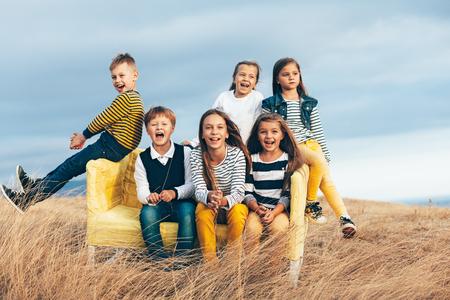 modelos hombres: Grupo de niños de la manera que usan ropa de estilo mismo de descanso en un sofá en el campo de otoño. Caída traje casual en color azul marino y amarillo. modelos 7-8, 8-9, 9-10 años que se sientan en un autobús al aire libre.