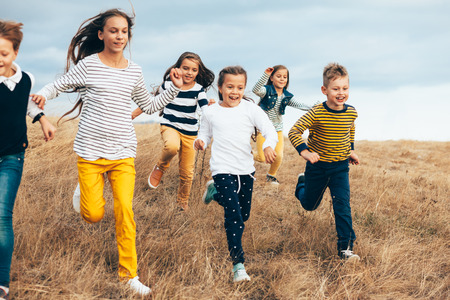Group of fashion children wearing same style clothing running in the autumn field. Fall casual outfit in navy and yellow colors. 7-8, 8-9, 9-10 years old models.