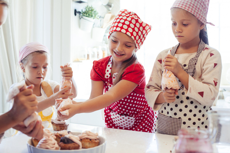decorate: Group of children cooking in the white kitchen. Kids wearing colorful aprons baking dessert at home.