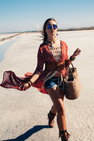 clothing model: Fashion model wearing bohemian chic clothing posing on the salt beach outdoor.