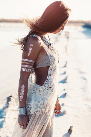 Beautiful girl wearing bohemian chic clothing with flash tattoo on her body posing on the shore in sunlight