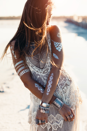 Beautiful girl wearing bohemian chic clothing with flash tattoo on her body posing on the shore in sunlight 스톡 콘텐츠