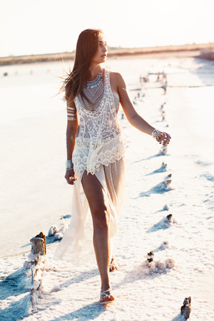 tanned girl: Beautiful girl wearing bohemian chic clothing with flash tattoo on her body posing on the shore in sunlight Stock Photo