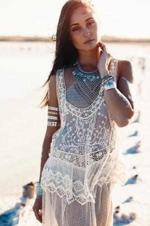 햇빛에 해안에 포즈 그녀의 시체에 플래시 문신과 보헤미안 세련 된 의류를 입고 아름 다운 소녀 스톡 콘텐츠