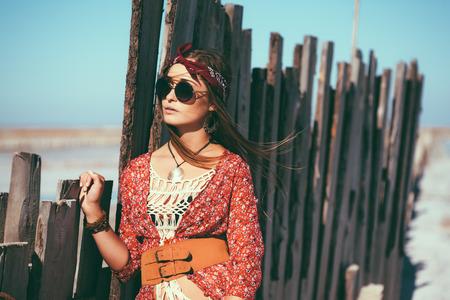 mujer hippie: Modelo de manera que el uso de ropa elegante bohemio presenta en la playa salada al aire libre. Foto de archivo