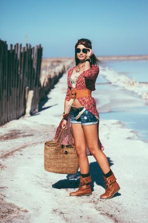 mimbre: Modelo de manera que el uso de ropa elegante bohemio presenta en la playa salada al aire libre. Foto de archivo
