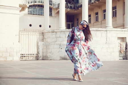 Plus size model wearing floral maxi dress posing on the city street. Young and fashionable overweight woman walking around town. Фото со стока