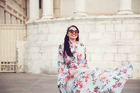 summer dress: Plus size model wearing floral maxi dress posing on the city street. Young and fashionable overweight woman walking around town. Stock Photo