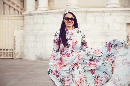 Plus size model wearing floral maxi dress posing on the city street. Young and fashionable overweight woman walking around town. Banque d'images