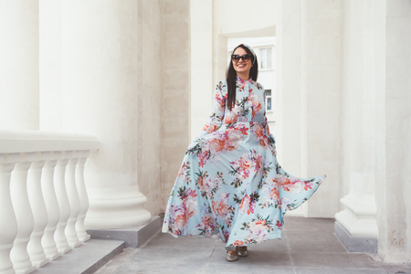 Plus size model wearing floral maxi dress posing on the city street. Young and fashionable overweight woman walking around town. Stock Photo