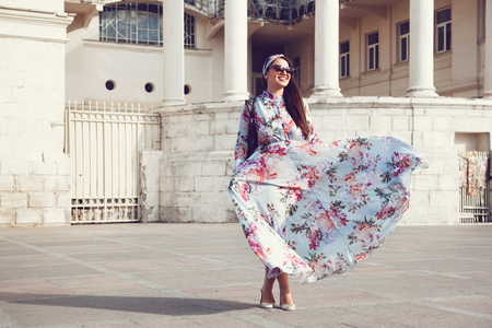 maxi dress: Plus size model wearing floral maxi dress posing on the city street. Young and fashionable overweight woman walking around town. Stock Photo
