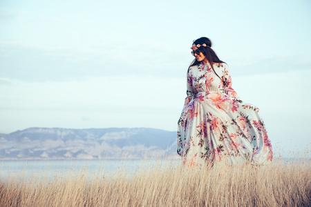 Plus size model draagt bloemen maxi jurk poseren in het veld. Jonge en modieuze overgewicht vrouw lopen op de wal. Stockfoto