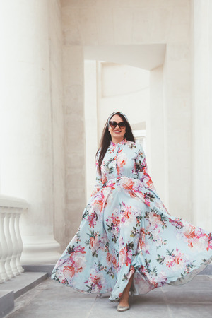 maxi: Plus size model wearing floral maxi dress posing on the city street. Young and fashionable overweight woman walking around town. Stock Photo