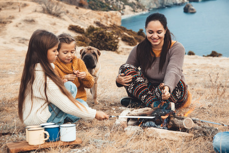 Family with dog sitting by the fire and frying sausages in mountains. Autumn hike in cold weather. Warming and cooking near flame together. photo