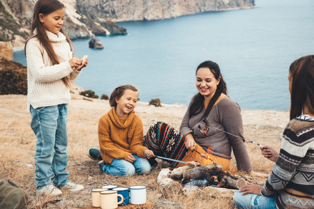 Family sitting by the fire and frying sausages in mountains on the sea shore. Autumn hike in cold weather. Warming and cooking near flame together. photo