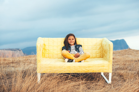 7 years old child sitting on a sofa in the autumn field outdoor. photo