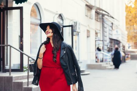 身に着けている赤いマキシ ドレス、黒革のジャケットと帽子で秋の街を歩いて若いスタイリッシュな女性。秋のファッション、エレガントな外観。