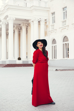 maxi: Young stylish woman wearing red maxi dress, black leather jacket and hat walking on the city street in autumn. Fall fashion, elegant look. Plus size model.
