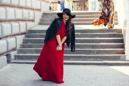 Young stylish woman wearing red maxi dress, black leather jacket and hat walking on the city street in autumn. Fall fashion, elegant look. Plus size model.
