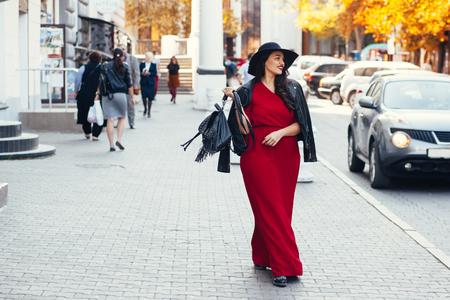 Jonge modieuze vrouw die rode maxi jurk, zwarte leren jas en hoed lopen op de stad straat in de herfst. Fall mode, elegante look. Plus size model.