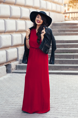 maxi dress: Young stylish woman wearing red maxi dress, black leather jacket and hat walking on the city street in autumn. Fall fashion, elegant look. Plus size model.