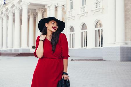 Giovane donna alla moda che porta il maxi abito rosso, giacca di pelle nera e un cappello che cammina sulla strada della città in autunno. Caduta di moda ed elegante. Modello più di formato. Archivio Fotografico
