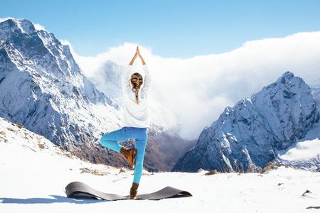 요가 연습 야외에서 겨울에 젊은 여자. 산 꼭대기에 눈이에서 운동을 streching. 추운 계절에 하이킹. 조용하고 조용한 전망.