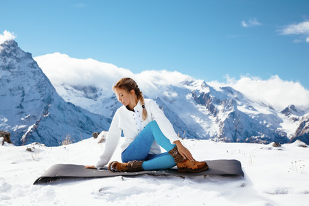 cold season: Young woman practicing yoga pose outdoors in winter. Streching workout in snow on top of mountain. Hiking in cold season. Calm and silent view.