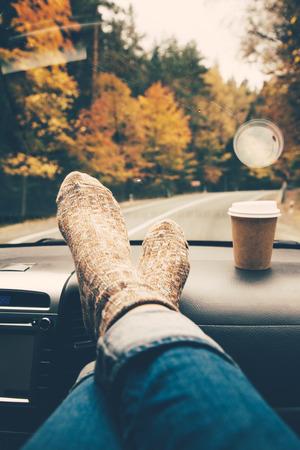 Vrouw voeten in warm sokken op de auto dashboard. Drinken weg te nemen koffie op de weg. Fall reis. dalingen van de regen op de voorruit. reisconcept vrijheid. Autumn weekend. Gefilterd foto.