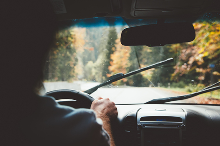 비가 날씨에 운전하는 사람 (남자). 가을 여행. 와이퍼는 앞 유리를 청소합니다. 자유 여행 개념입니다. 가 주말. 스톡 콘텐츠