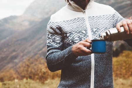 주석 잔을 들고 등산객 스웨터를 입고. 아침 야외에서 따뜻한 차 또는 커피를 마시는 남자. 하이킹 개념 캠핑. 산에서 가을 여행, 추운 날씨. Noface 사진