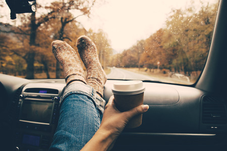 Kobieta nogi w ciepłych skarpetkach na desce rozdzielczej samochodu. Picie zabiera kawę na drodze. Wycieczka jesienią. Krople deszczu na przedniej szybie. Koncepcja podróży wolności. Jesienny weekend. Filtrowane zdjęcie.