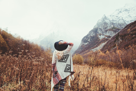 Boho woman wearing hat and poncho standing by the mountain. Cold weather, snow on hills. Winter hiking. Wanderlust. Stock Photo
