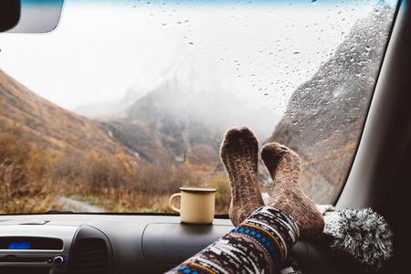 Woman legs in warm socks on car dashboard. Drinking warm tee on the way. Fall trip. Rain drops on windshield. Freedom travel concept. Autumn weekend in mountains. Standard-Bild