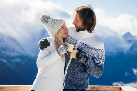 Loving couple resting and drinking morning coffee together in snow outdoor. Winter holidays in mountains. Man and woman wearing knitted clothing having fun on weekends. Фото со стока