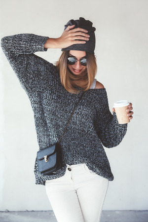 oversize: Trendy hipster girl photo in fashion urban outfit. Grey oversize sweater, hat and sunglasses. Swag street style. Drinking coffee in take away paper cup.