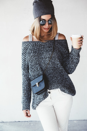 oversize: Trendy hipster girl photo in fashion urban outfit. Grey oversize sweater, hat and sunglasses. Swag street style. Drinking coffee in take away paper cup