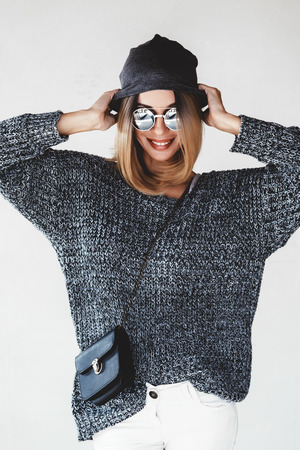 Trendy hipster girl photo in fashion urban outfit. Grey oversize sweater, hat and sunglasses. Swag street style. Stock Photo