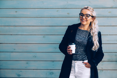 Woman wearing black coat, white pants, hipster glasses drinking take away coffee in paper cup standing against cafe wall on city street. Fall casual fashion, elegant everyday look. Plus size model. Banco de Imagens